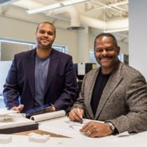 image of Curt and Jonathan Moody standing at table with drawings and a building model